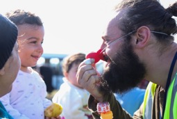 Picture of man with red plastic clown noise and a child smiling