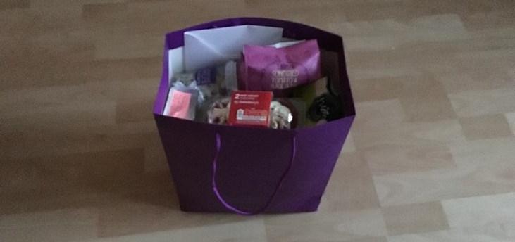 A purple gift bag full of treats