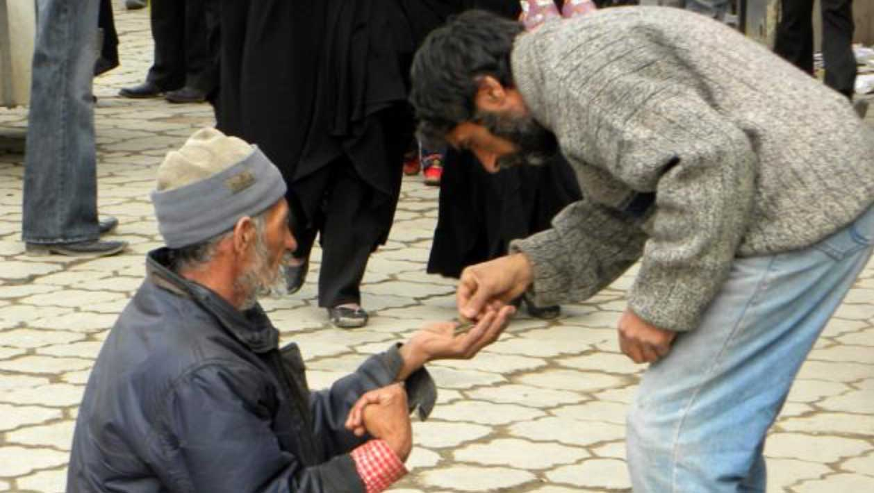 A man giving to another in need
